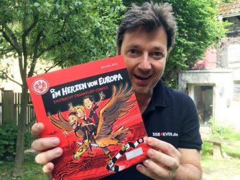 Michael Apitz präsentiert stolz den neuen Sammelband der Eintracht-Comics